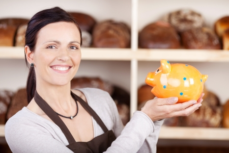 saleslady: Smiling woman baker in apron holding a golden piggybank Stock Photo