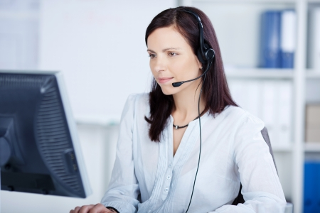 headset woman: Beautiful call center agent browsing the internet on her computer