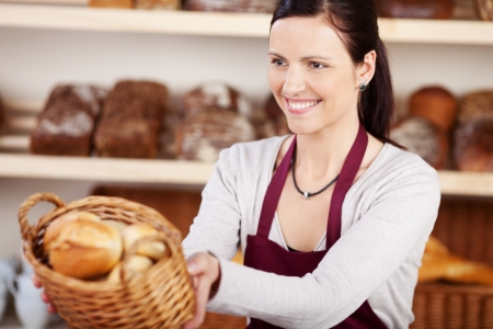 saleslady: Woman working in a bakery offering a customer a basket of assorted bread and rolls with a friendly smile, focus to the woman