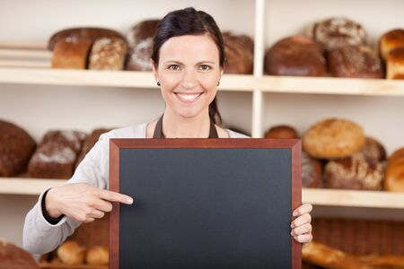 endorsing: Pretty worker in a bakery pointing to a blank chalkboard with a friendly smile with copyspace on the board for your message or advertisement