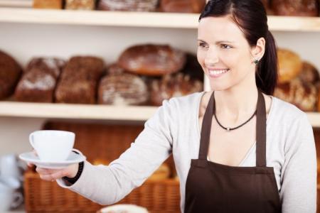 bread shop: Amichevole giovane donna in un grembiule che serve una calda tazza di caff� in una panetteria in un contesto di pagnotte di pane specialistiche