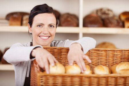 saleslady: Smiling attractive female assistant selecting rolls in a bakery from a large wicker basket and smiling at the camera