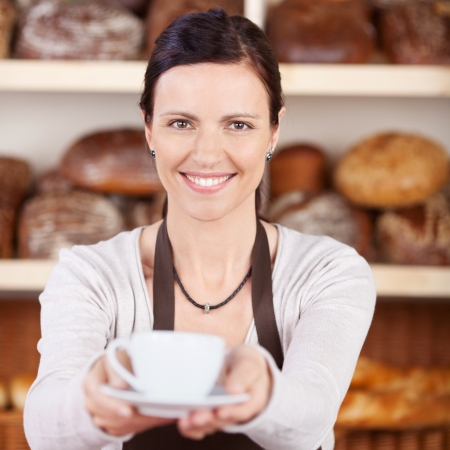 selling service smile: Friendly smiling woman worker serving a hot cup of coffee in a bakery with a backdrop of shelves full of bread