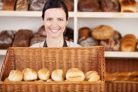 Female bakery worker standing holding a basket of freshly baked rolls in her hands with a friendly smile on her face photo