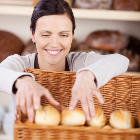 bakers: Smiling happy woman worker with a friendly smile sorting fresh rolls in a bakery in a large wicker basket