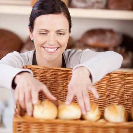 panadero: Trabajador sonriente mujer feliz con una sonrisa clasificar pan fresco en una panader�a en una cesta de mimbre Foto de archivo