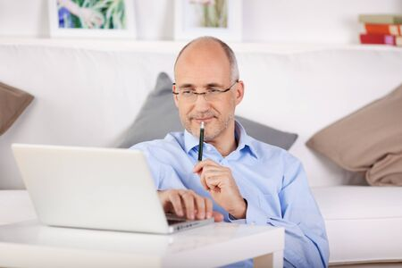 bald man: Businessman working through his laptop while leaning on the couch Stock Photo