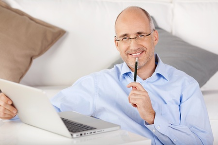 Smiling man working with pen on his chin at home with laptop photo