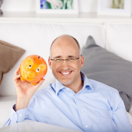 thrift box: Smiling man holding an orange piggy bank in the living groom