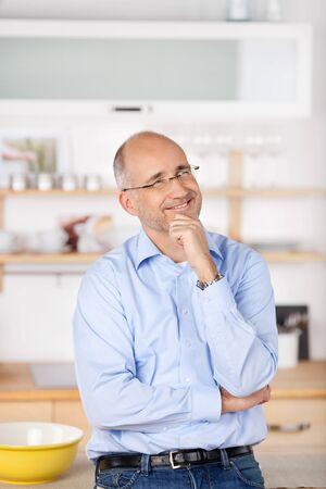 Porträt der lächelnden Mann, der oben und Denken etwas zu Hause Standard-Bild