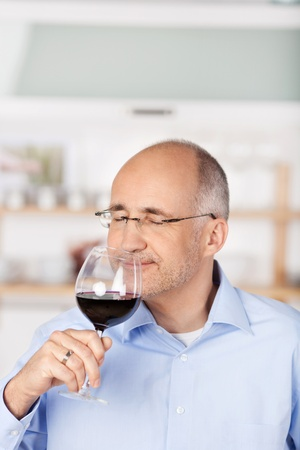 Bald handsome man smelling the red wine
