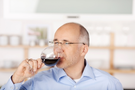 oenology: Mid age man drinking red wine at home Stock Photo