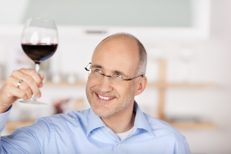 Smiling mid age man looking at the red wine