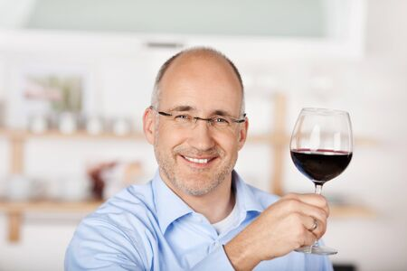 Smiling man showing the red wine at home photo
