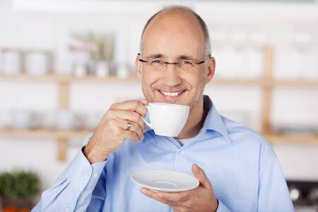 tomando café: Feliz mediados hombre de la edad de beber café en casa Foto de archivo