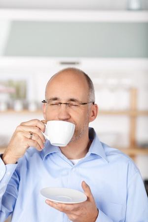 hombre tomando cafe: Apuesto hombre de tomar caf� en el fondo de cocina Foto de archivo