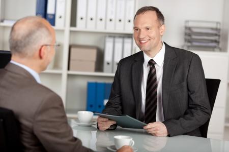 interview job: Dos hombres de negocios que tiene una conversaci�n dentro de la oficina