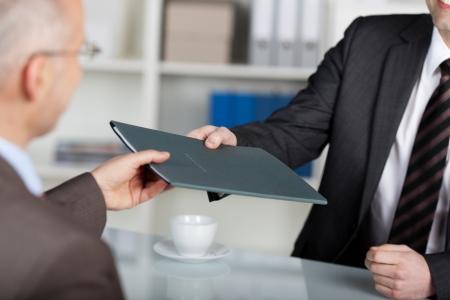Portret van een manager geven map naar een mannelijke kandidaat in zijn kantoor