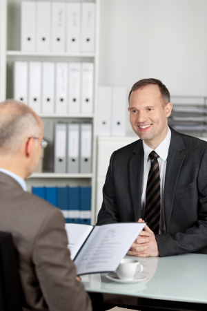 applicant: The manager reviewing information of the applicant in his office Stock Photo