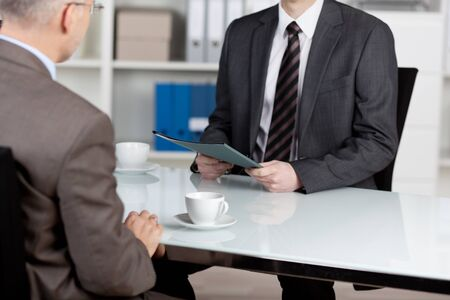 Manager interviewing a male applicant in his office photo