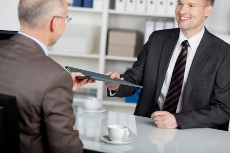 Smiling applicant present his information to the employer photo