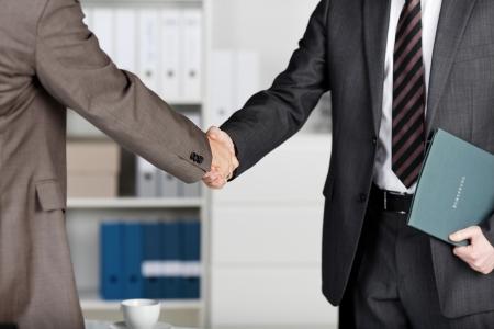 compromiso: Detalle de dos hombres de negocios dándose la mano en la oficina Foto de archivo