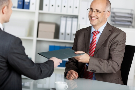 human resources: Businessman giving his job application to the employer inside the office Stock Photo