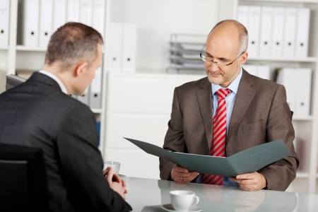 interrogation: Senior businessman read the application in the office Stock Photo