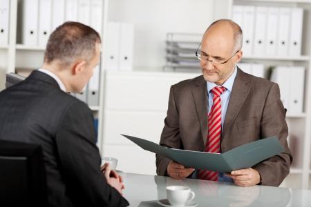 entrevista de trabajo: Senior empresario ley� la solicitud en la oficina