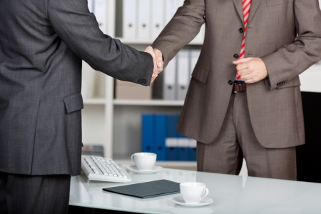 deals: Two successful business partner shaking hands in the office Stock Photo