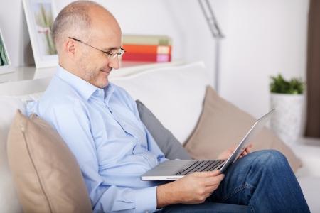 bald men: Smiling senior man browsing the internet in the living room