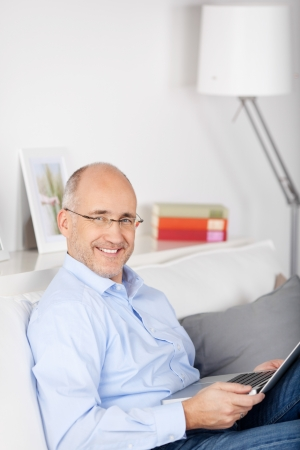 Portrait of relaxing man sitting on the couch with laptop photo