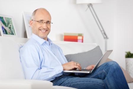 bald man: Hombre sonriente sentado en el sofá y navegar por internet Foto de archivo