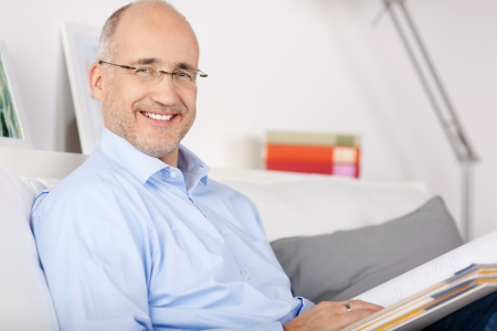Smiling senior man reading file folder on the couch Stock Photo - 21146952
