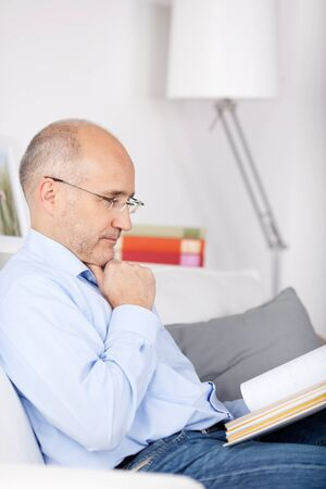 Senior man sitting on the couch and reading a book