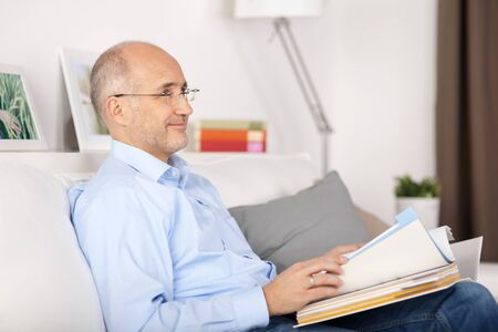 ring binder: Smiling man reading book in the living room