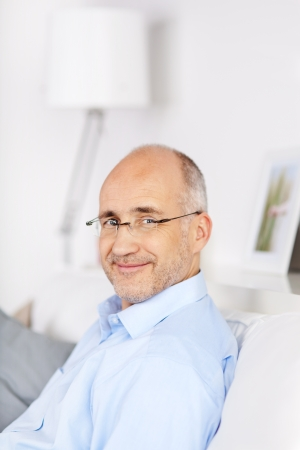 Smiling bald man sitting and resting on the couch at home Stock Photo - 21145762