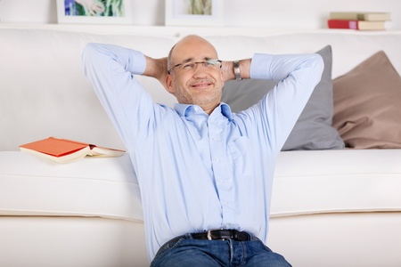 man behind: Smiling man relaxing and sitting in the living room