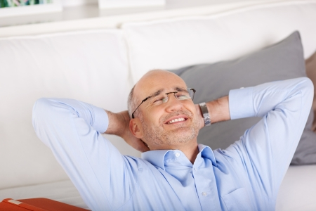 Smiling man relaxing and leaning on couch inside the living room photo