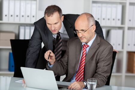 Two male business colleagues working together in an office discussing information on the screen of a laptop computer photo