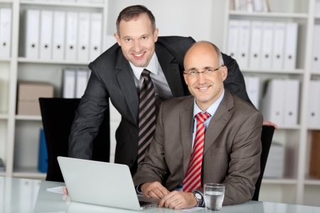 Two businessmen in an office smiling at the camera while working together behind a laptop computer photo