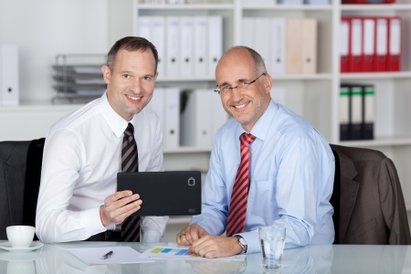 Two Colleagues working with tablet inside the office
