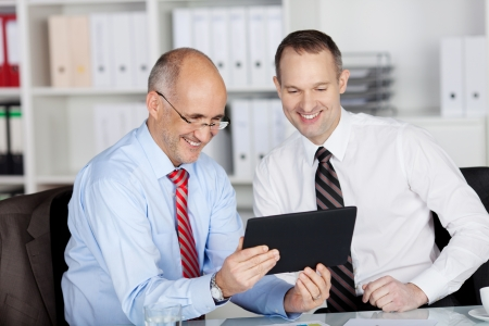Happy businesspeople browsing through ipad tablet in the office photo