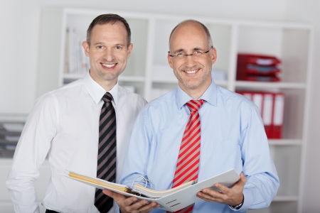 businesspersons: Two businesspersons working with file folders in the office