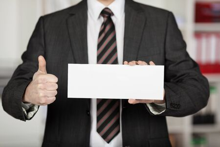 Unrecognized businessman showing thumbs up and holding white envelope photo