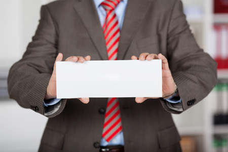 place card: Close up shot of unrecognized businessman showing a white card