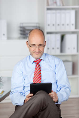 Bald businessman browsing the internet through tablet computer photo
