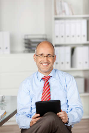 Smiling man using ipad tablet at the office background photo
