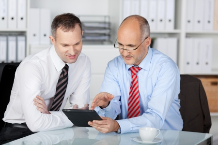 Two businesspeople working with tablet computer at the office photo