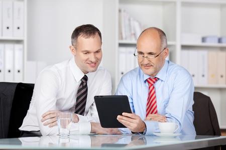 monitoreo: Dos hombres de negocios que buscan algo que usa la tableta